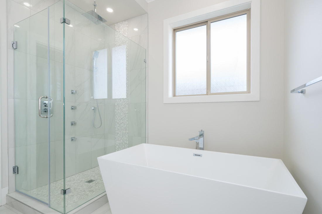 Bathroom glass shower, body sprays, freestanding rectangular tub.