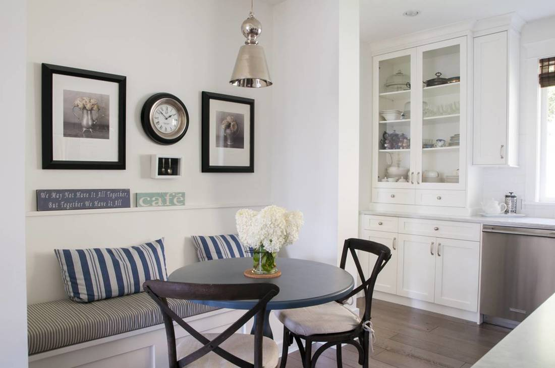 Dining room nook, built in seating, white cabinets, white walls.